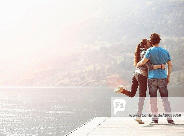 Junge Frau küsst Freund am Pier am Mergozzo-See  Verbania  Piemonte  Italien