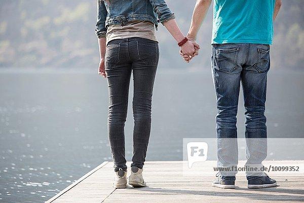 Ausschnitt aus der Rückansicht eines jungen Paares  das am Pier des Mergozzo-Sees  Verbania  Piemonte  Italien  Händchen hält.