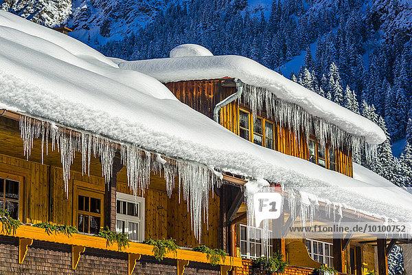 Lange Eiszapfen hängen vom schneebedeckten Dach eines Bauernhauses  Stillachtal  bei Oberstdorf  Allgäu  Bayern  Deutschland  Europa