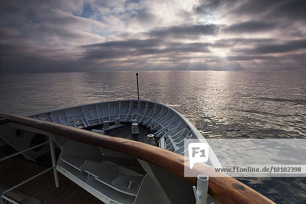 Blick über den Ozean vom Bug eines Kreuzfahrtschiffes im Morgengrauen.
