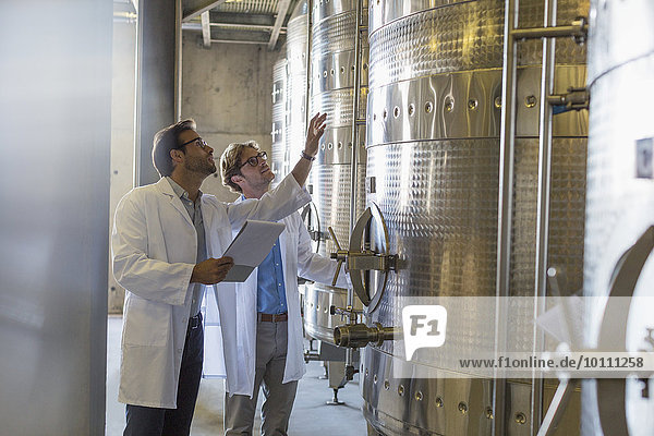 Winzer in Labormänteln prüfen Fässer im Weinkeller