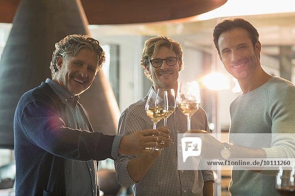 Portrait lächelnde Männer beim Weißweintrinken im Weingut