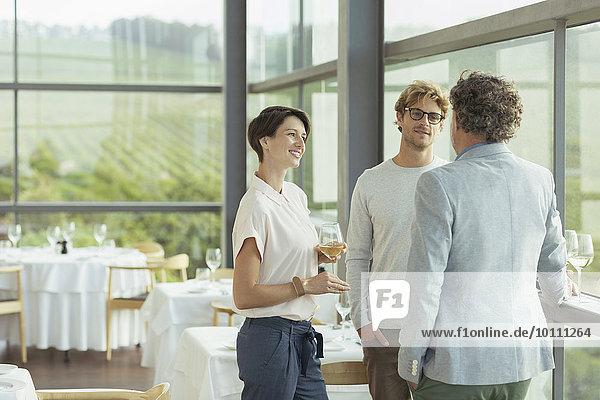 Freunde reden und trinken Wein im Speisesaal des Weingutes