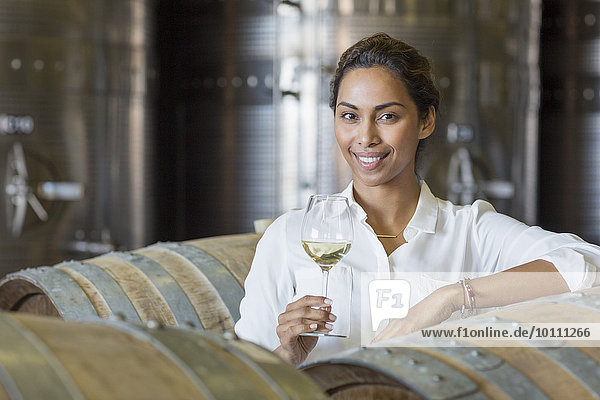 Portrait selbstbewusster Winzer beim Weißweintrinken im Weinkeller