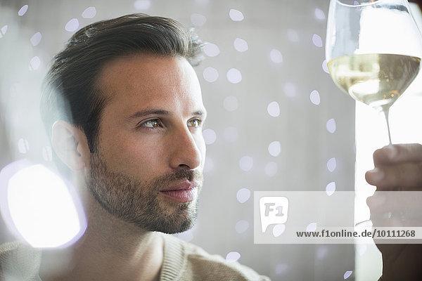 Nahaufnahme eines seriösen Mannes bei der Untersuchung von Weißwein