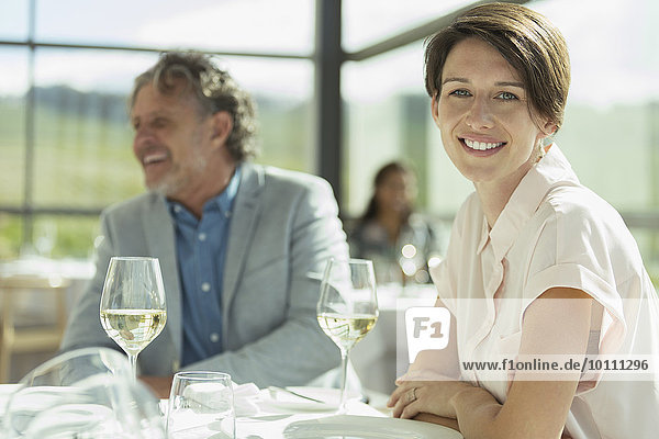 Portrait lächelnde Frau beim Weintrinken im sonnigen Restaurant