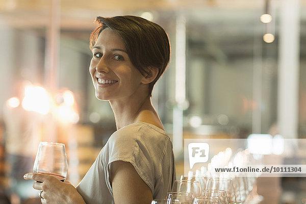 Portrait lächelnde Frau Weinverkostung im Weinkeller