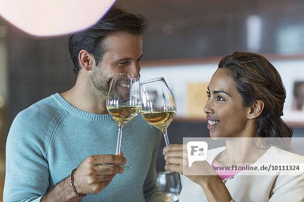 Lächelndes Paar röstende Weißweingläser