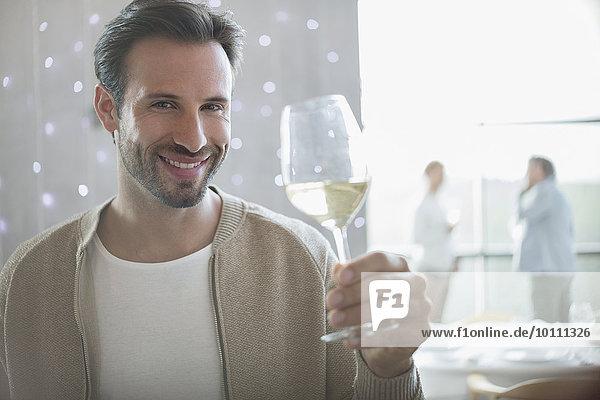 Portrait lächelnder Mann trinkt Weißwein im Restaurant
