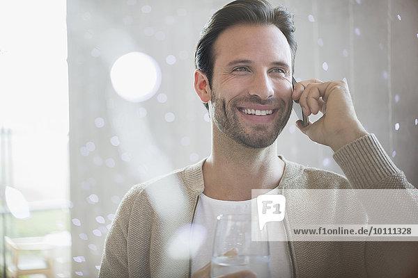 Lächelnder Mann trinkt Wasser und spricht am Handy