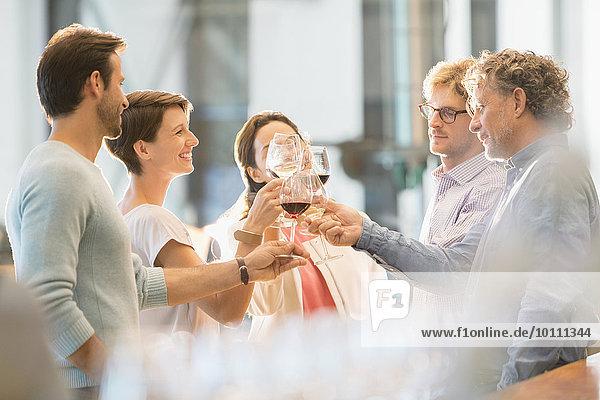 Freunde toasten Weingläser