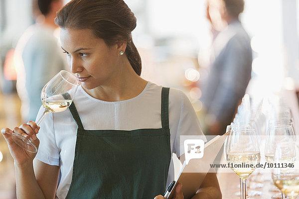 Weingutmitarbeiter riecht Weißwein im Verkostungsraum