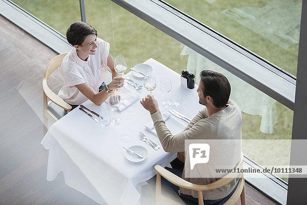 Paar Toastweingläser am Restauranttisch am Fenster
