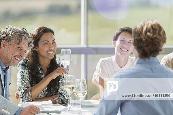 Freunde trinken Wein und reden am Restauranttisch