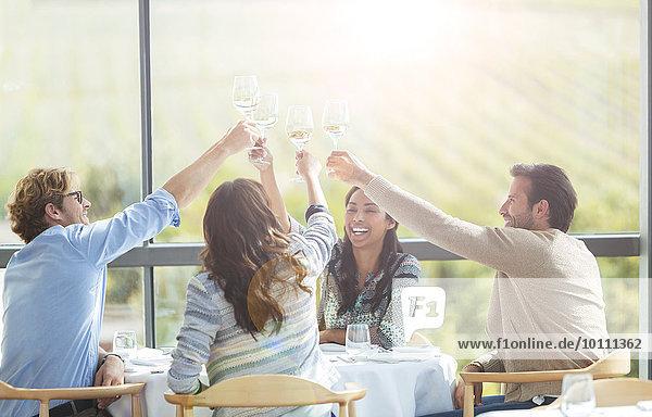 Freunde toasten Weingläser am Esstisch des Weingutes
