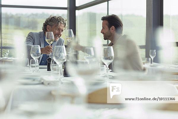 Männer toasten Weingläser am Restauranttisch