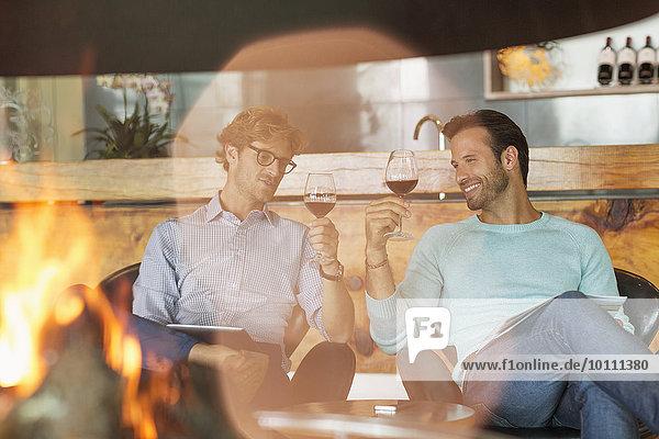 Weinverkostung der Männer am Kamin im Weinkeller
