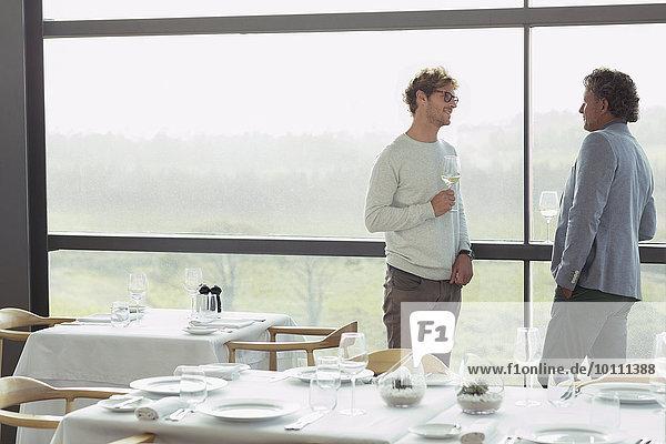 Männer trinken Wein am Restaurantfenster