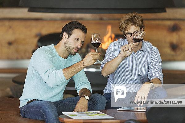 Männer Weinprobe Rotwein im Verkostungsraum des Weingutes