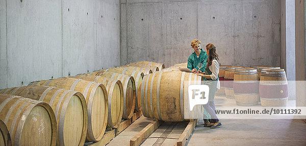 Winzer im Weinkeller bei Fässern im Gespräch