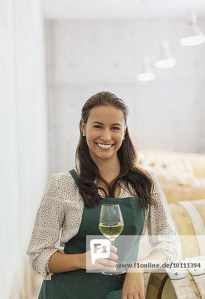 Porträt souveräner Winzer mit Weißwein im Keller