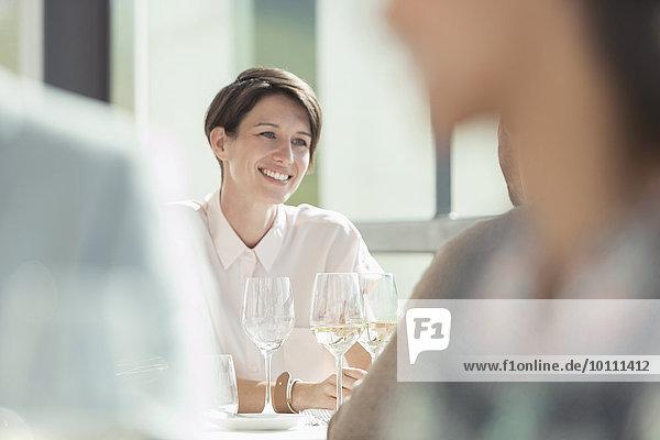 Lächelnde Frau trinkt Weißwein im sonnigen Restaurant