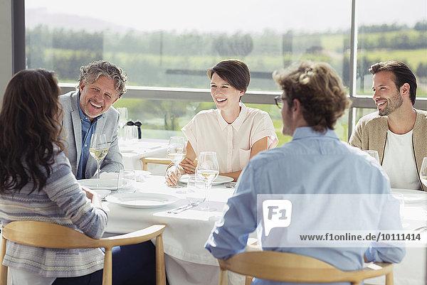 Freunde trinken Weißwein und reden am sonnigen Restauranttisch