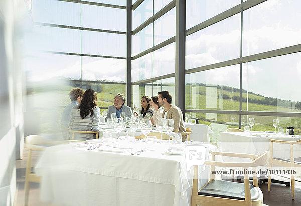 Freunde sitzen am Tisch im sonnigen Speisesaal des Weingutes