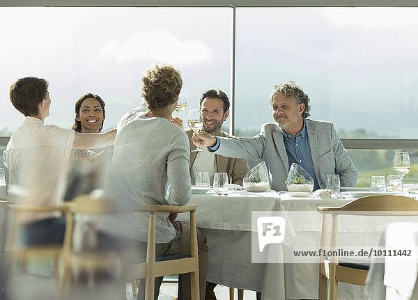 Freunde toasten Weingläser am sonnigen Restauranttisch