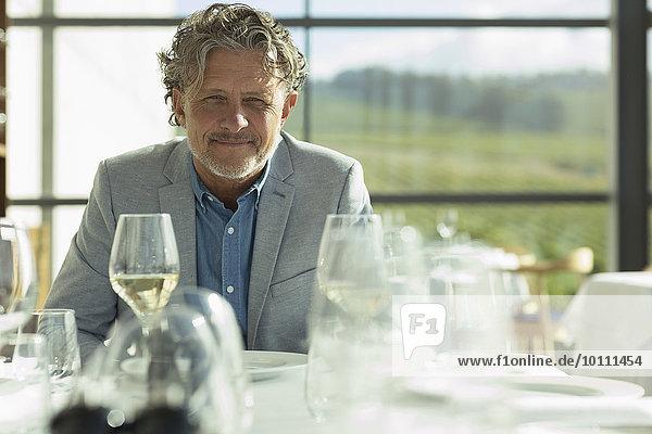 Porträt souveräner Mann mit Weißwein am sonnigen Restauranttisch