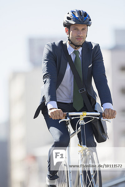 Businessman in suit commuting on bicycle with helmet