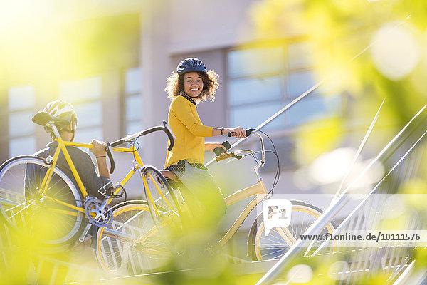 Lächelnde Frau mit Fahrrad in der Stadt