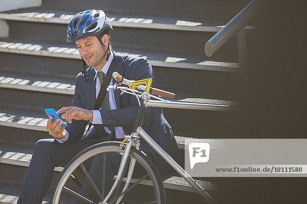 Businessman in suit with bicycle and helmet texting with cell phone on stairs