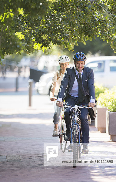 Businessman in suit and helmet riding bicycle on path