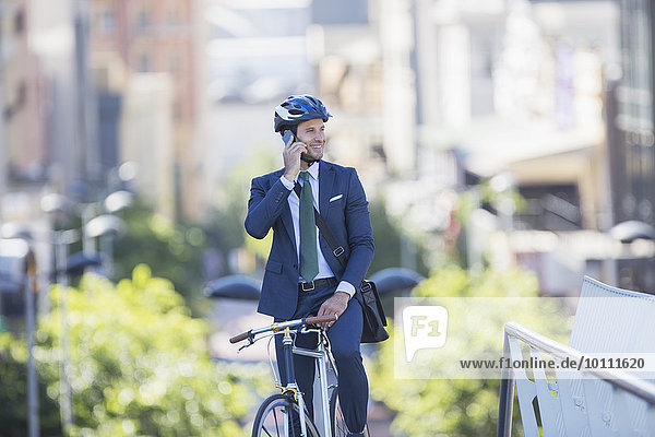 Businessman in suit and helmet sitting on bicycle talking on cell phone in city