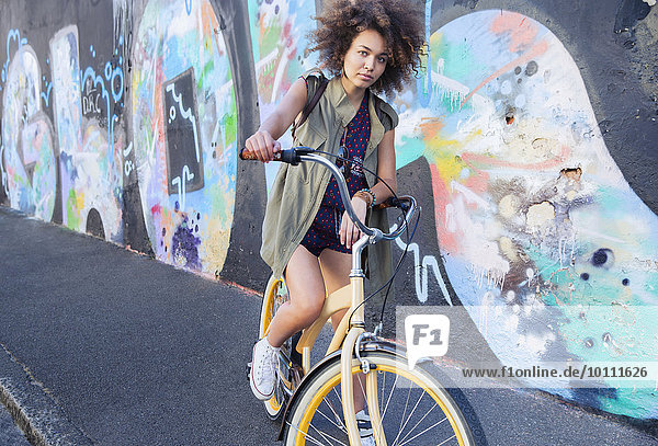 Portrait serious woman with afro on bicycle next to urban graffiti wall