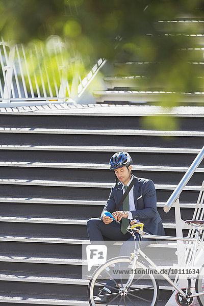 Businessman with helmet and bicycle texting with cell phone on urban stairs
