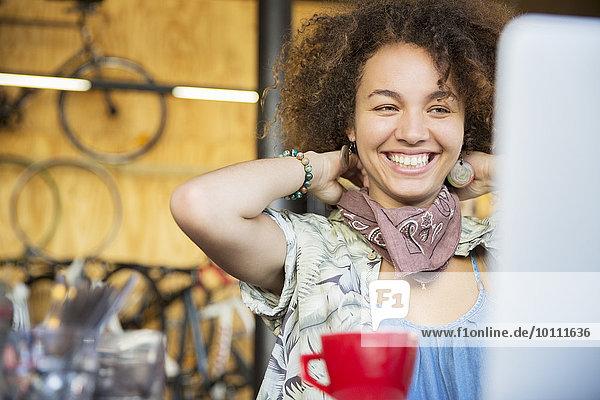 Lächelnde Frau am Laptop im Fahrradgeschäft beim Anpassen des Halstuches