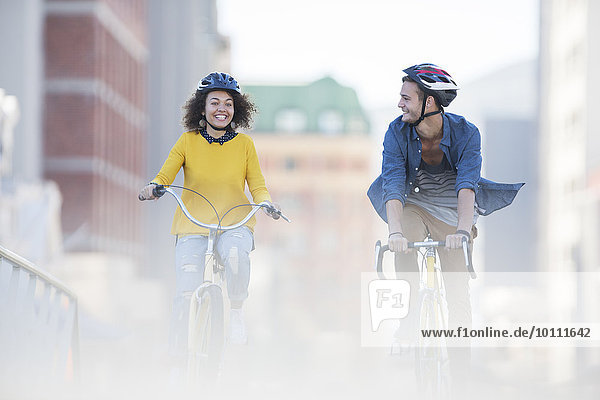 Young couple riding bicycles in city
