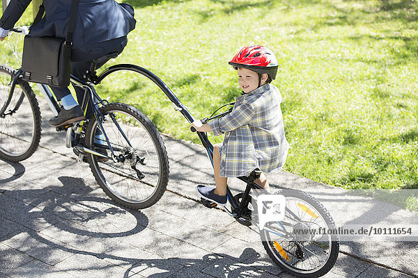 Boy riding tandem bicycle with businessman father in sunny park