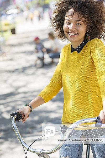 Portrait lächelnde Frau auf dem Fahrrad im Park