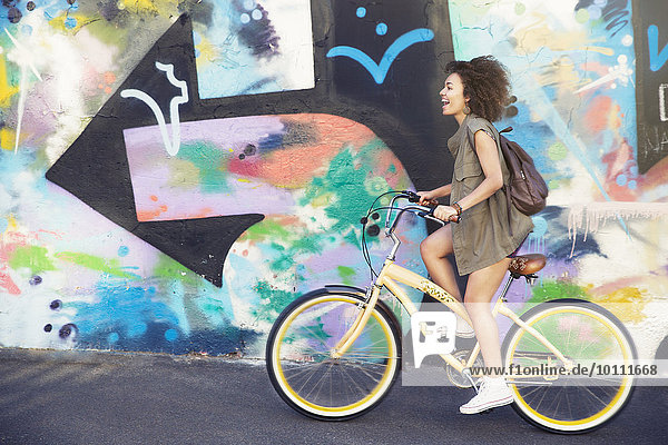 Frau fährt mit dem Fahrrad an einer mehrfarbigen Graffiti-Wand entlang