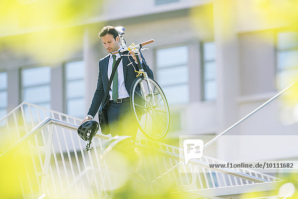 Businessman in suit carrying bicycle in city