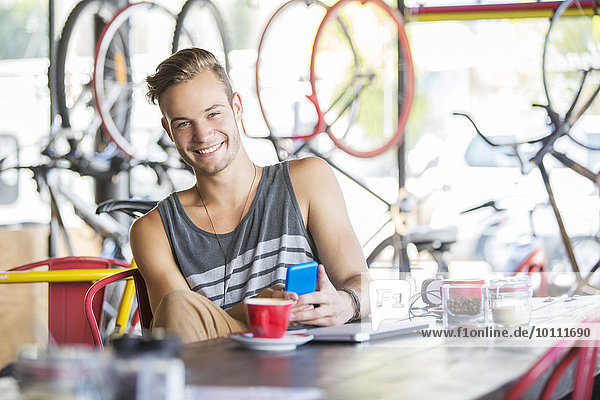 Portrait smiling man with coffee and cell phone in bicycle shop