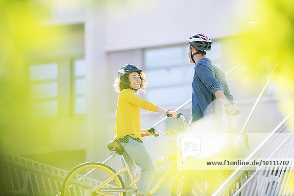 Man and woman with helmets on bicycles talking
