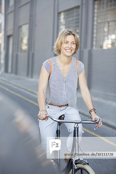 Lächelnde blonde Frau beim Fahrradfahren auf der Stadtstraße
