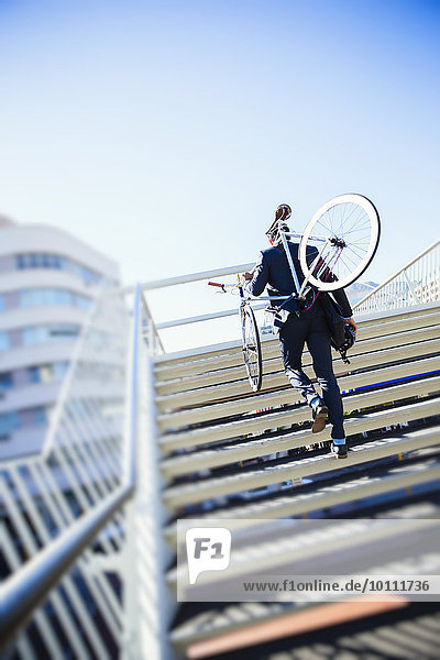 Businessman carrying bicycle up urban stairs under sunny blue sky