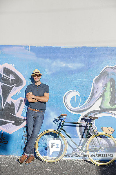 Portrait smiling man in hat and sunglasses leaning on urban graffiti wall next to bicycle