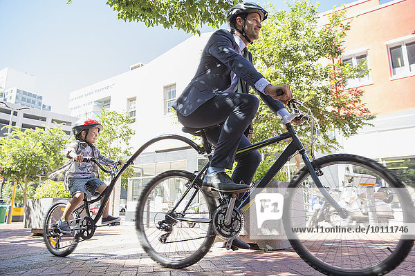 Businessman father in suit riding tandem bicycle with son on urban sidewalk