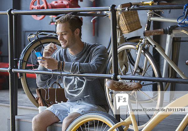 Young man texting with cell phone near bicycles at railing